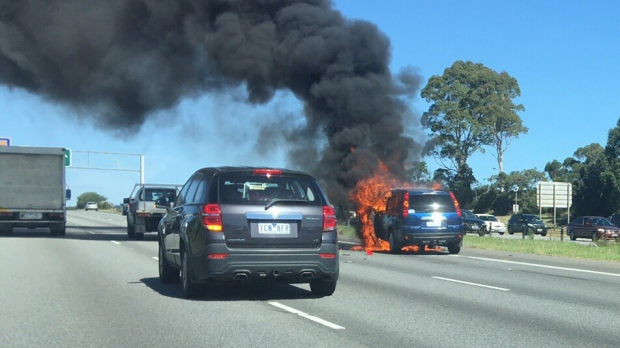 Article image for Car bursts into flames after crash with motorbike on Monash Freeway