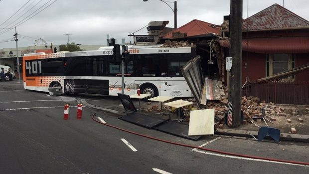 Article image for Bus smashes through takeaway shop at North Melbourne after colliding with a truck