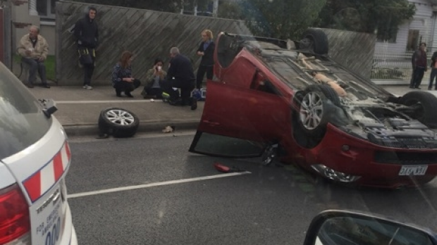 Article image for Paramedics are treating the driver of a car that flipped onto it's roof at Coburg