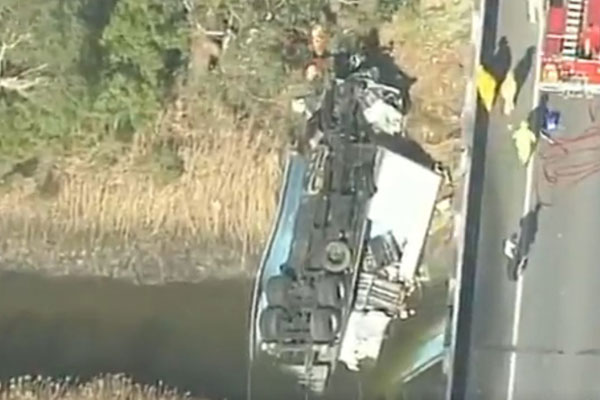 Article image for Driver critical after truck hits barriers, rolls off a bridge on the Bass Highway