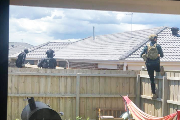 Article image for Woman finds armed police officers in her backyard executing a warrant on her neighbour