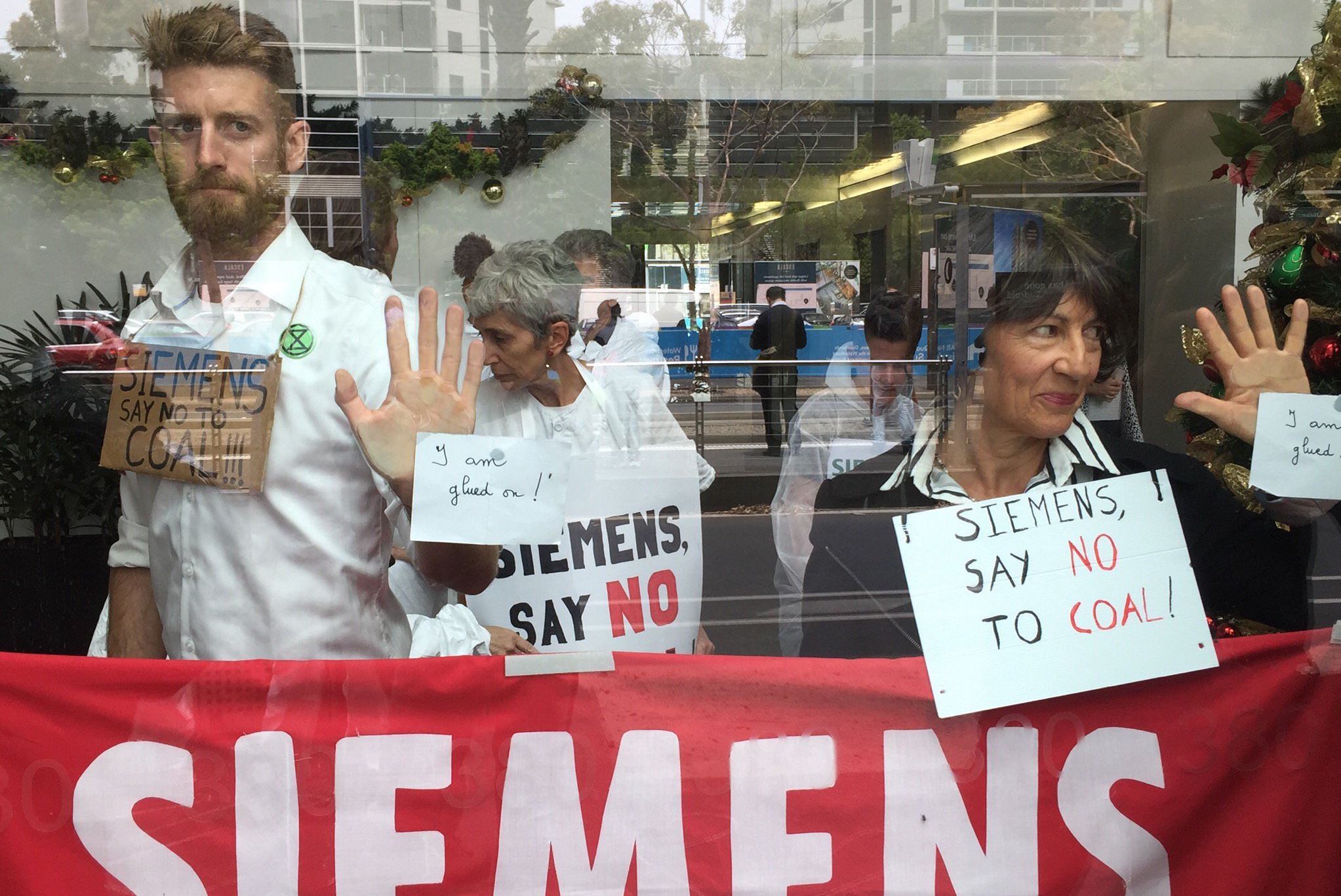 Article image for Activists glue themselves to Siemens office in protest against tech giant's Adani mine contract