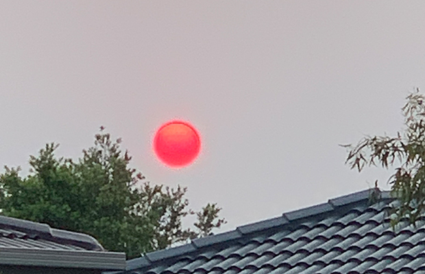 Article image for Photos: Eerie 'red orb' starts another smoky day in Melbourne