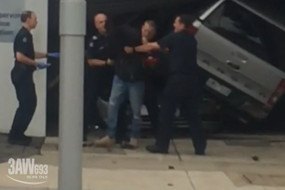 Article image for VIDEO: Man ploughs ute into police station, headbutts police officer in 'very scary' violent outburst
