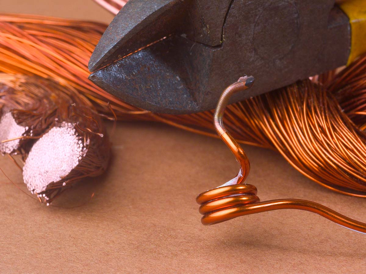 Pliers cutting through thick copper cable