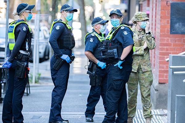 Police in masks standing outside Melbourne quarantine hotel