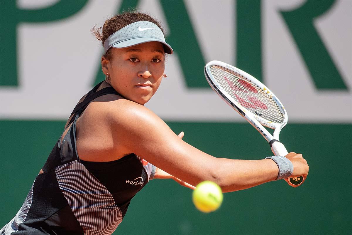 Naomi Osaka swings a tennis racquet at a ball at Roland Garros