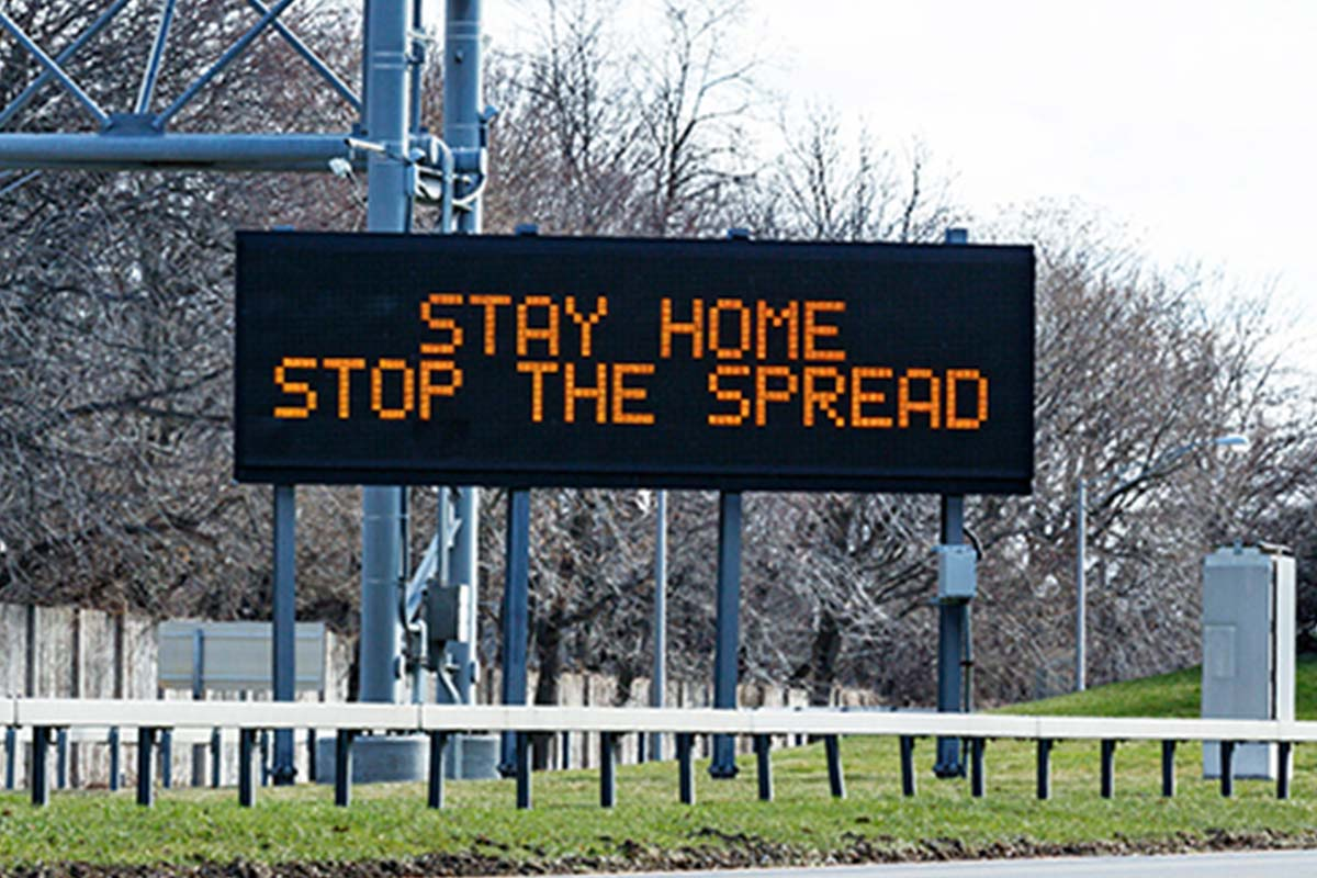 Sign on roadside which says 'stay home, stop the spread'