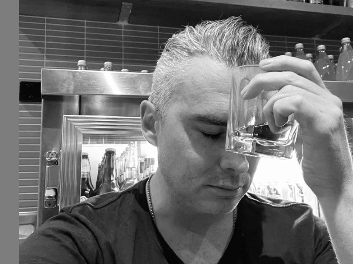 Owner of Charles and Gamon, Eamon Walmsley, holds a glass to his head and looks dismayed