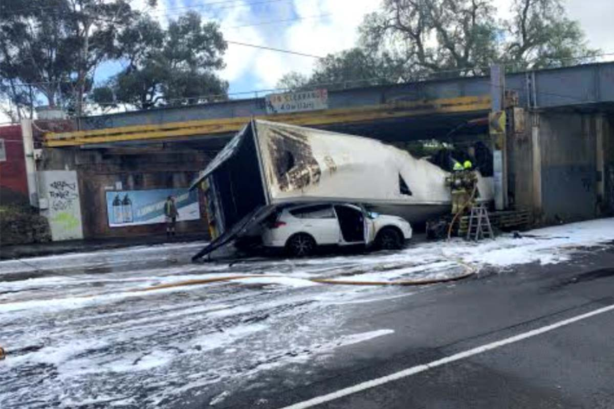 Article image for Truck collides with Essendon rail bridge, catches fire and rolls on a car