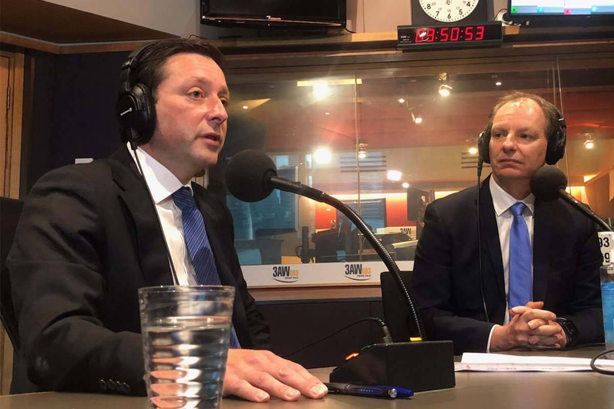 Matthew Guy and David Southwick in the 3AW studio wearing headphones and sitting in front of microphones