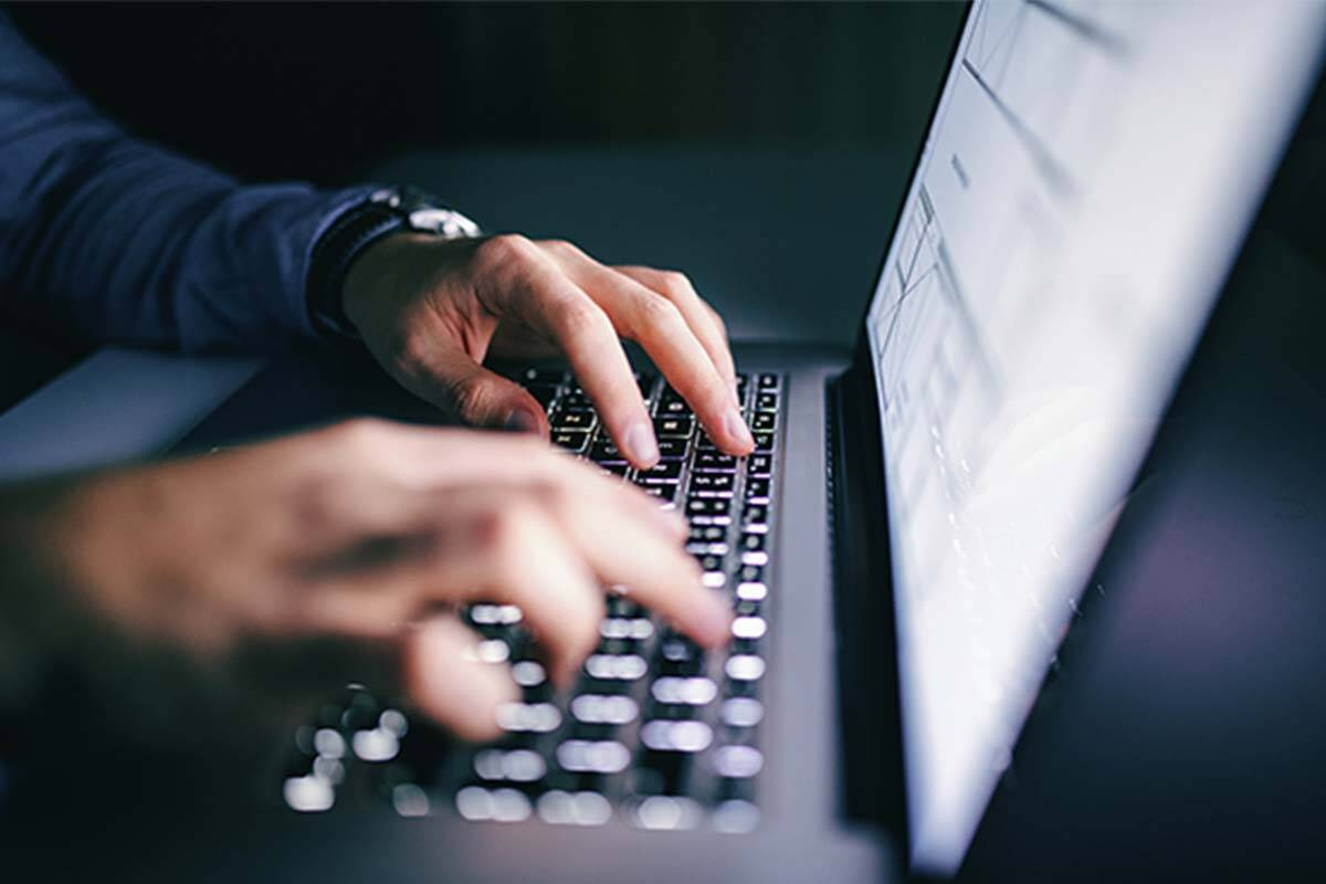 Man's hands typing on keyboard in dark room
