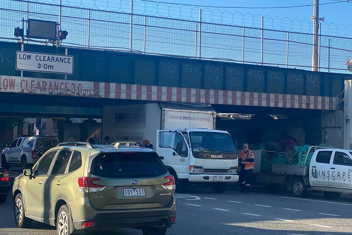 A truck is stuck under the Montague Street Bridge